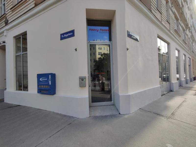 Außenansicht unseres Geschäftslokal am Ilgplatz 2 in 1020, Eckeingang in einem Altbau mit beiger Fassade und grauem Sockel, links an der Wand hängt ein Schwalbe Schlauchautomat